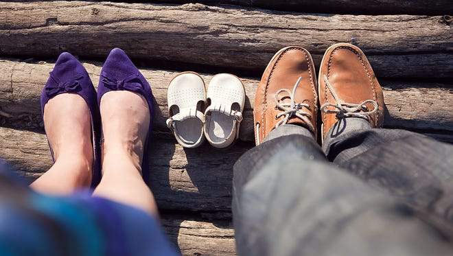 Male and female feet with shoes for a baby.