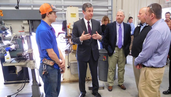 Gov. Roy Cooper talks about the demand for workers in advanced manufacturing during a visit Tuesday to the classroom at Madison High School where students learning machining. Among those listening is former student Josh Bradley, left, who is now employed at Advanced Superabrasives International
