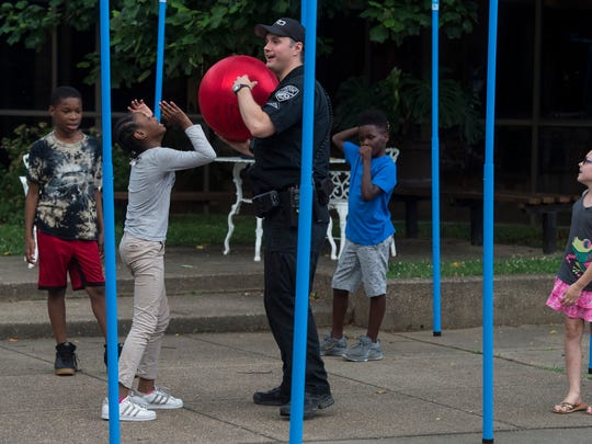 Officer Josh Brewer plays a game with kids during the
