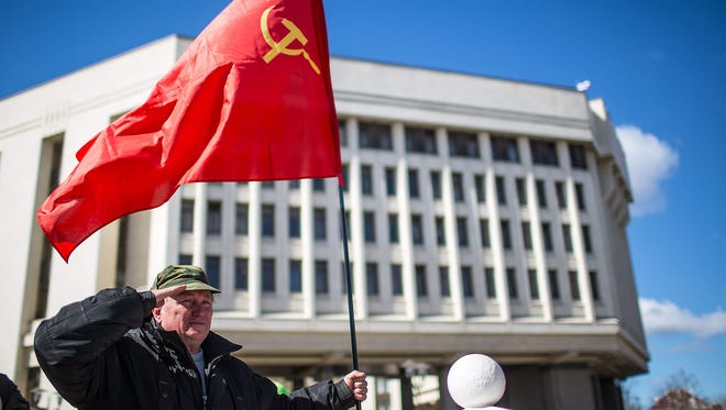A man holding a Soviet Russian flag salutes in front of the parliament building in Simferopol, Crimea, Ukraine. Crimeans voted to leave Ukraine and join Russia.