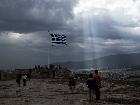 A Greek flag waves at the ancient Acropolis hill in