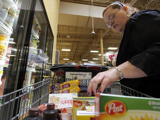 Annette Spain arranges items in her shopping cart at the Kroger on University Parkway.