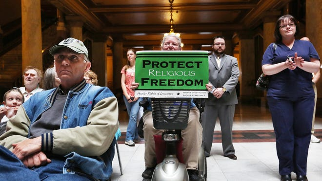 Cindy Holmes, Mechanicsburg, holds up a sign at the Indiana Pastors Alliance rally in the north atrium of the Indiana Statehouse on Monday, April 27, 2015. More than 150 people showed up to express their opposition to the changes Indiana lawmakers made to the Religious Freedom Restoration Act that Gov. Mike Pence signed earlier this month.