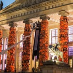 Workers attach life jackets used and discarded by refugees and migrants to the facade of the Konzerthaus concert hall in Berlin as part of an art installation by Chinese artist Ai Weiwei.