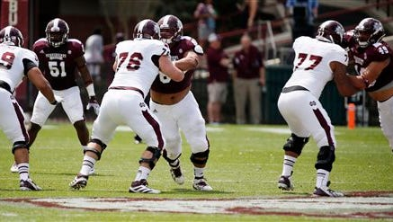 Mississippi State White offensive linemen Archie Muniz (59), Jake Thomas (76), and Rufus Warren (77) tie up Maroon defenders in the second half of their spring NCAA college football game, Saturday, April 12, 2014, in Starkville, Miss. Maroon won 41-38. (AP Photo/Rogelio V. Solis)