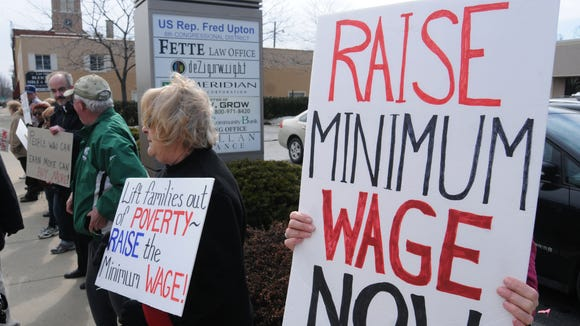 Residents gather during a minimum wage rally outside the district offices of U.S. Rep. Fred Upton, R-Mich., in St. Joseph, Mich., Tuesday, April 1, 2014. Raise Michigan needs to gather 258,000 valid signatures by late next month to put before the Legislature a measure that would gradually raise the state's minimum wage from $7.40 to $10.10 an hour by 2017 and automatically increase it with inflation in future years. (AP Photo/The Herald-Palladium, Don Campbell) ORG XMIT: MIBEN102