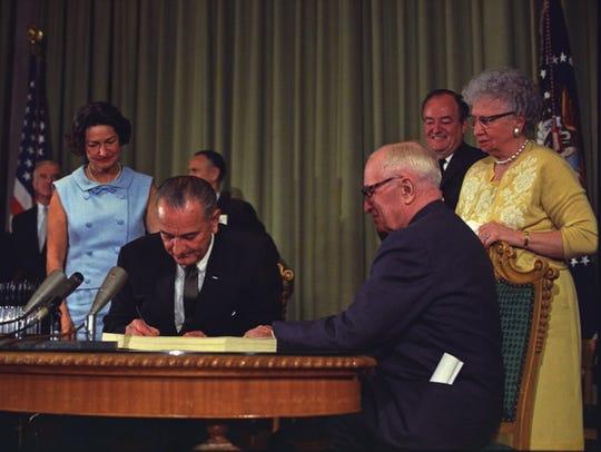 President Lyndon B. Johnson signs the Medicare Bill.