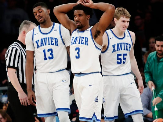 Xavier's Naji Marshall (13), Quentin Goodin (3) and J.P. Macura (55) react after Macura was called for a foul during overtime of an NCAA college basketball game against Providence in the Big East men's tournament semifinals Friday, March 9, 2018, in New York. (AP Photo/Frank Franklin II)