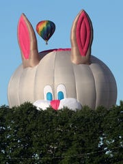 A hot air balloon shaped like a rabbit peeks out from