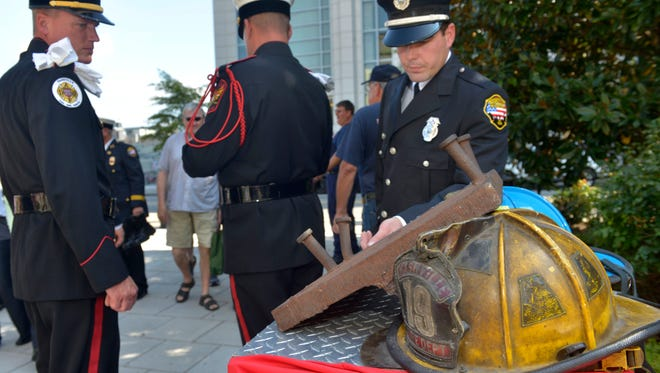 The Nashville Fire Department unveils a part of the World Trade Center in a special ceremony at the Schermerhorn Symphony Center Sept. 11, 2015 in Nashville, Tenn. The piece was given to the fire department and will be used in a firefighter memorial at the training academy sponsored by TriStar Health.