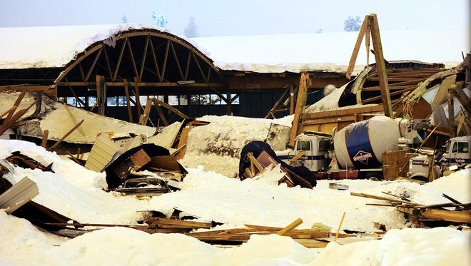 This photo taken Jan. 11, 2016 shows debris covering several large trucks after a roof collapsed at KorPine mill building in Bend, Oregon.