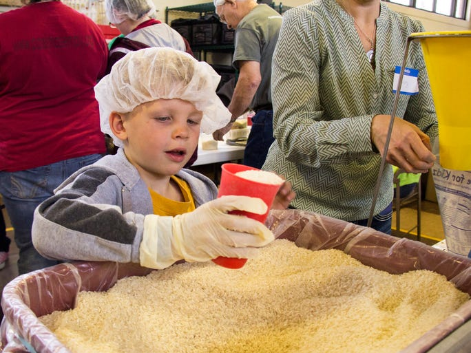Ben Mayo, 5, prepares a scoop of rice for a meal that will be shipped across the world to those in need. He was one of hundreds of volunteers who packed over 70,000 meals as part of the Day of Hope event at York and Campbell elementary schools Saturday.