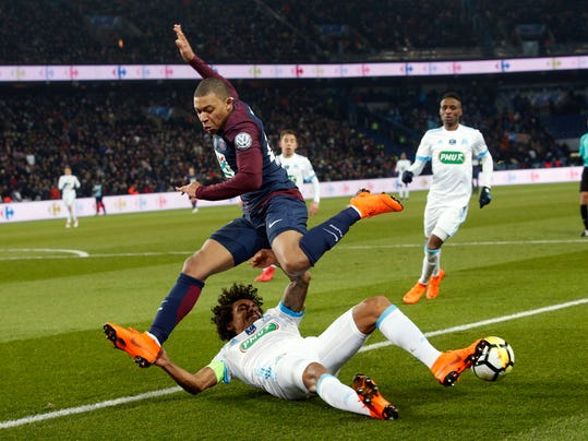 PSG's Kylian Mbappe challenges for the ball with Marseille's Luiz Gustavo Dias during the French Cup soccer match between Paris Saint-Germain and Marseille at the Parc des Princes Stadium, in Paris, France, Wednesday, Feb. 28, 2018. (AP Photo/Thibault Camus)