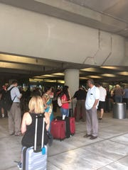 Travelers wait after a suspicious package prompts a