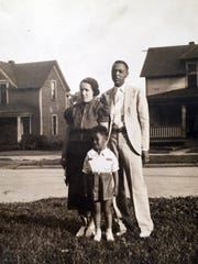 A young Roger Maxwell, around age 5, is shown standing with his parents, Margaret and Artice, in front of their home in Marshalltown. (The family's house is visible in the background, at left.) Because many hotels at the time would not permit black guests, the family took in black travelers.