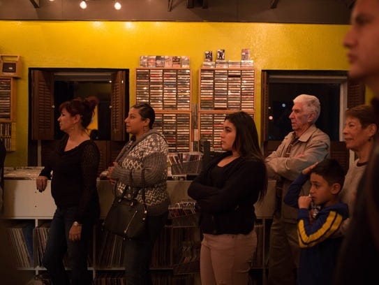 Attendees watch local folk artist Alison Reynolds perform at Eyeconik Records & Apparel on Dec. 1.
