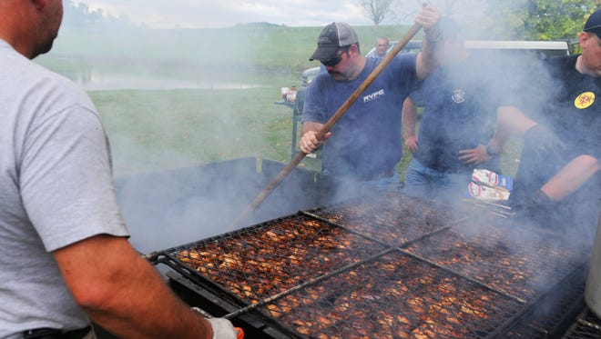 Capt. Bruce Brooks of the Raphine Volunteer Fire Company barbecues some chicken. Mike Tripp/The News Leader Capt. Bruce Brooks of the Raphine Volunteer Fire Company stirs up the embers while helping barbecue the chicken during the 7th Annual Cyrus McCormick Farm Mill Day near Raphine on Saturday, Oct. 6, 2012.