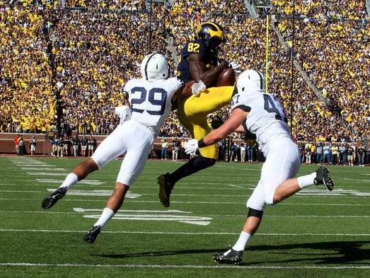 Michigan #82 Amara Darboh hangs on to the catch despite