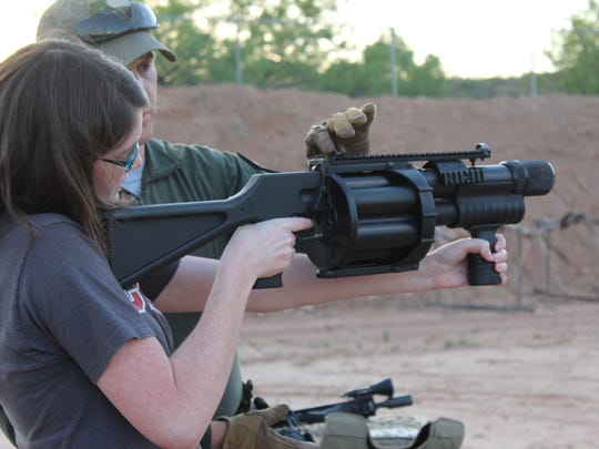 Rachel Blake, an assistant district attorney for Taylor County, gets pointers from Sgt. Clay Grother, a SWAT team member, on how to fire the Penn Arms 40 mm launcher at Tuesday night's Citizens Police Academy class. Getting hit by munitions fired from this weapon is similar to being struck by a 90 mph fastball.