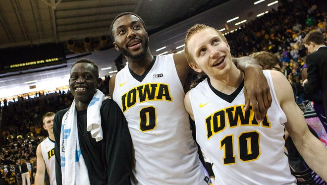 Iowa teammates Peter Jok (3), senior Gabe Olaseni (0) and Mike Gesell (10) celebrate the victory following the Iowa vs Northwestern game at Carver-Hawkeye Arena in Iowa City on Saturday, March 7, 2015. The Hawkeyes (22-10, 13-6) beat the Wildcats (15-17, 6-13) 69-52 to win their 6th straight.