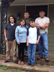 Members of the Ramos family posed for a portrait outside their home in Memphis shortly before the parents' departure in 2015.  From left, front: Isaias Ramos, Cristina Vargas and Dustin Ramos. Back row, from left: Mario Ramos and Dennis Ramos.