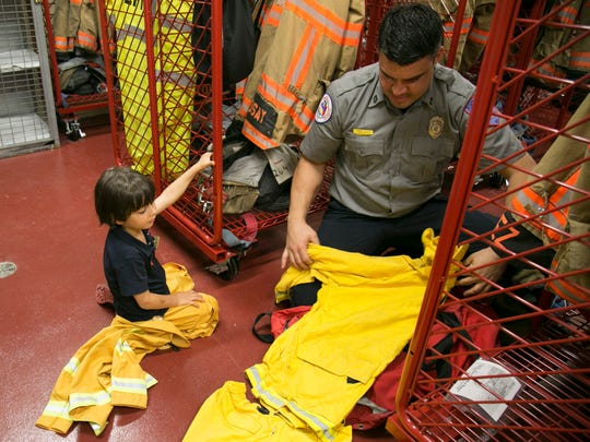 Fort Myers firefighter Jorge Perez shows Elias Blagojevic, 5, his gear on Monday during a tour of Station 1 in downtown Fort Myers.