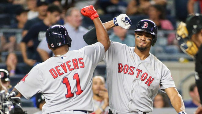 Red Sox rookie Rafael Devers is congratulated by teammate Xander Bogaerts after hitting a game-tying home run in the ninth inning on Sunday.