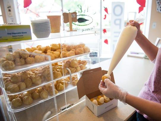 Dominae Worstall fills fresh créme puffs inside Chloe's Créme Puffs in Pitman.