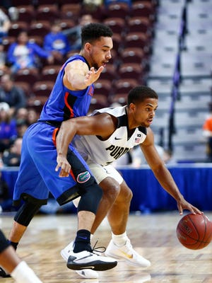 Purdue Boilermakers guard P.J. Thompson (R) dribbles the ball against Florida Gators guard Chris Chiozza (L) during the first half at Mohegan Sun Arena.