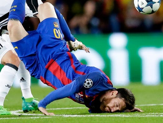 Barcelona's Lionel Messi lands on his face aftera challenge