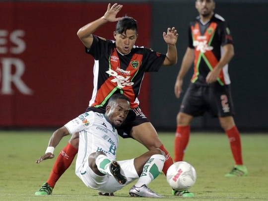 Club Leon's Dario Burbano falls to the turf while being defended by Juan Castro of FC Juárez on Wednesday at Southwest University Park. Leon won the friendly 2-0.