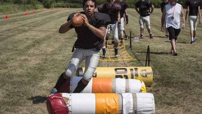 Cardinal Mooney's Quincy Greenia runs drills during football practice Aug. 12, in Marine City.