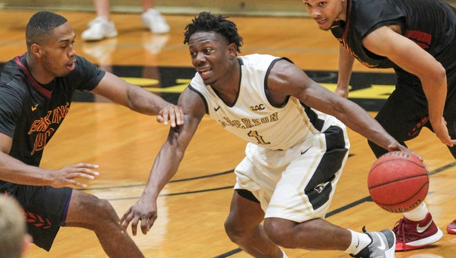 Anderson junior guard Maurice Howard, middle, dribbles around Erskine junior Fineto Lungwana during the 2016-17 season.