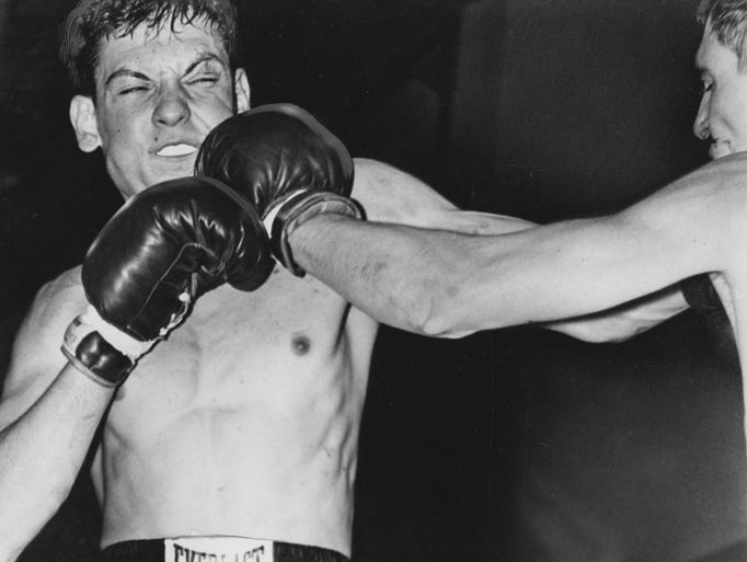 Steve Piccione flinches as he absorbs a stinging left jab from Paul Love during a 147 pound novice bout of the Golden Gloves in 1965