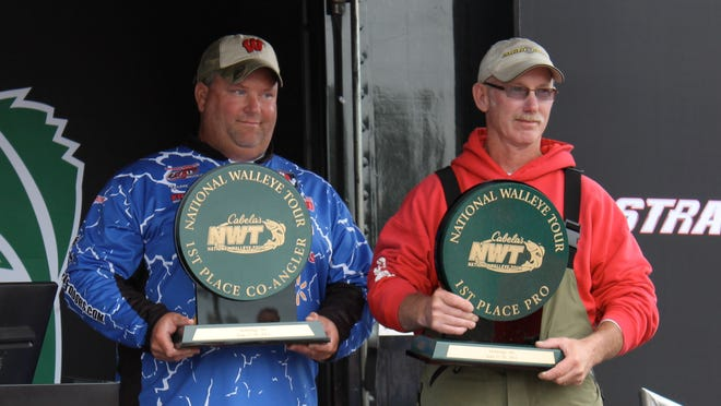 First-place co-angler Tyrone Larson, left, of Amherst and first-place pro-angler Wade While, right, pose with their respective trophies at the Cabela's National Walleye Tour event at Mobridge, S.D. on June 29, 2014.