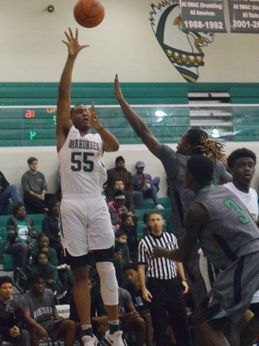 Peabody Magnet High School's Dwight Simon (55, left) shoots over two Bossier City High School defenders Tuesday, Dec. 4, 2017.