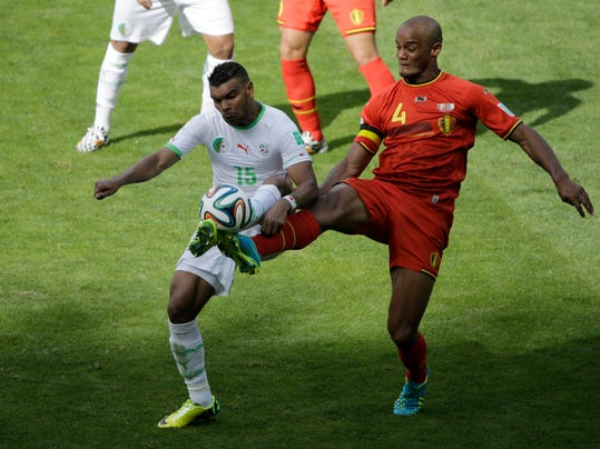 Algeria's El Arbi Hillel Soudani, left, and Belgium's Vincent Kompany fight for the ball during the group H World Cup soccer match between Belgium and Algeria at the Mineirao Stadium in Belo Horizonte, Brazil, Tuesday, June 17, 2014. (AP Photo/Sergei Grits)