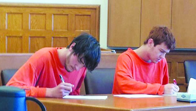 In a photo from Nov. 12, 2014, Thomas A. Hartman, 20, left, and Matthew A. Franjose, 19, both of Green Bay, Wis.,  fill out paperwork while awaiting arraignment in 95A Judicial District Court in Menominee, Mich. The men were each charge with felony home invasion-first degree, which carries a possible 20-year prison sentence and/or fines and costs of $5,000. The two men were allegedly involved in breaking into a home Monday morning in Mellen Township which resulted in the death of a third man, who was shot by the homeowner.