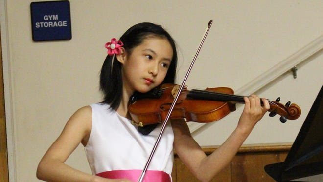 "Mt. Horeb School fifth-grade violinist Maya Yie prepares to present her ""Genius Hour"" project at the Board of Education meeting on April 24."