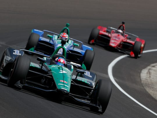 The No. 7 car that Jay Howard will drive in Sunday's Indianapolis 500 leads two others out of a turn during a practice session. CSU's One Cure program has the primary sponsorship position on Howard's car for this year's race.