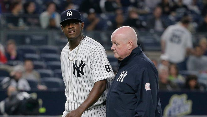 New York Yankees pitcher Luis Severino, left, walks off the field with head trainer Steve Donohue after giving up a two-run home run to Chicago White Sox's Jimmy Rollins during the third inning of a baseball game Friday, May 13, 2016, in, New York.