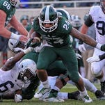 Michigan State running back Gerald Holmes (24) surges ahead against Penn State on Saturday.