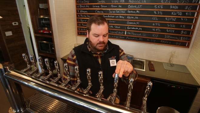 Beer monger Zander McKernan pours a glass of Captain Lawrence Sun Block Wheat Ale at Brew & Co. in Bedford Hills.