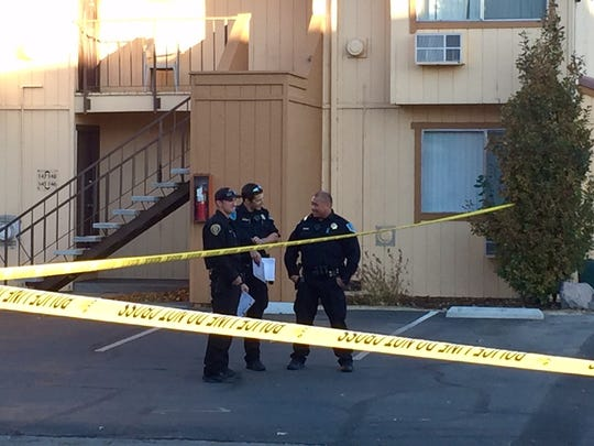 Sparks police officers are seen standing behind police tape at Home Suites Apartments. Police were investigating a shooting on Nov. 11, 2017.