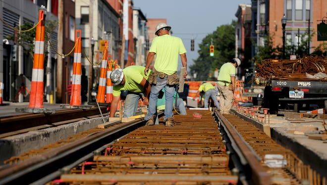 Prus Construction workers check the streetcar tracks on 12th Street in Over-the-Rhine during this past summer. The question of who will operate the streetcar once it's running could create another fight.