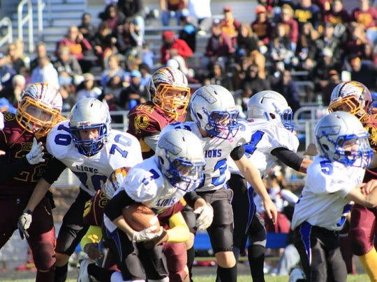 Canton Lions JV players Justin Rogers (70), Dominic Johnson (53), Antonio Correa (94) and Dylan Fleming (5) block for ball carrier Carson Sampson (7).