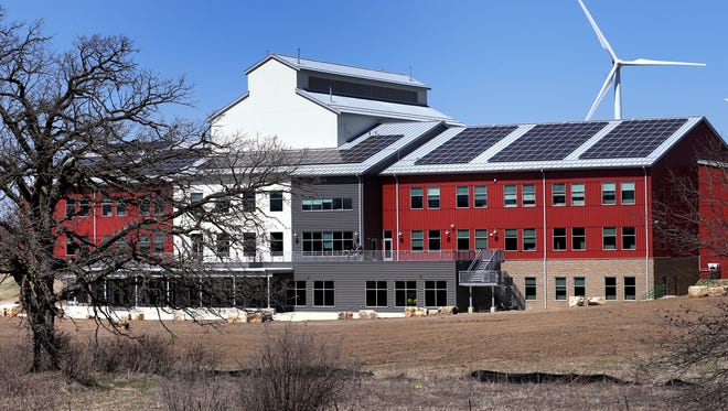 In this April 18, 2016 photo, the new Organic Valley office building in Cashton, Wis., is equipped with solar panels which contribute to the buildings exclusively green power supply. Organic Valley is planning a major investment in solar electricity that could substantially increase Wisconsin's solar capacity and reduce electric bills for rural consumers.