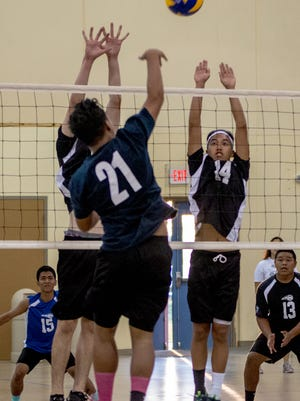 John Cano (14) attempts to block a spike by an Okkodo High School player.Virgilio Valencia/For Pacific Daily News