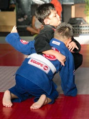 Jeremiah Duenas, in black gi, tries submission moves