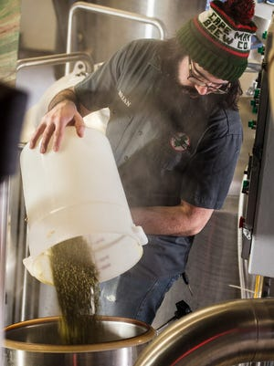 Brian Hink adds hops to a beer in honor of Pope Francis' visit to Philly.